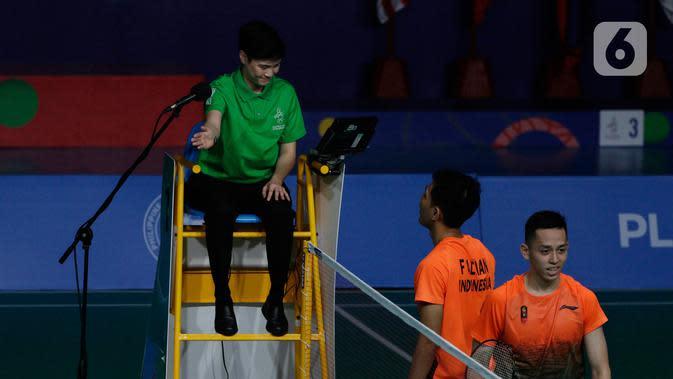 Ganda putra Indonesia, Fajar Alfian/Muhammad Rian Ardianto melakukan protes saat melawan pasangan Malaysia, Aarron Chia/Soh Wooi Yik pada final bulutangkis beregu putra SEA Games 2019 di Multinlupa Sport Center, Rabu (4/12/2019). Fajar / Rian kalah 17-21 dan 13-21. (Bola.com/M Iqbal Ichsan)