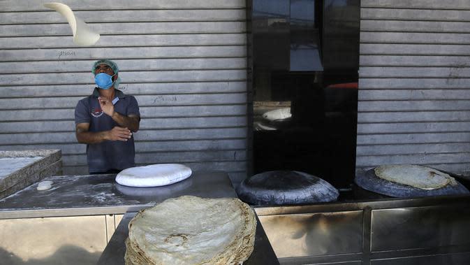 Seorang pria mengenakan masker saat membuat roti selama bulan suci Ramadan di sebuah toko di Kota Gaza, Palestina, Jumat (1/5/2020). (MOHAMMED ABED/AFP)
