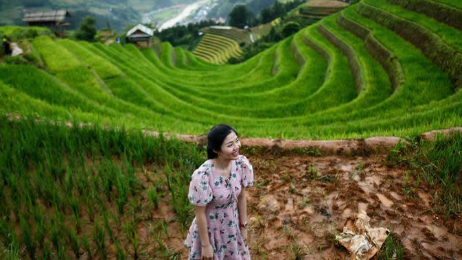 Seorang perempuan berfoto dengan latar belakang sawah terasering di distrik Mu Cang Chai, Vietnam pada 18 September 2020. Pesawahan terasering di Mu Cang Chai merupakan destinasi-destinasi wisata yang atraktif dan menyerap kedatangan banyak wisatawan domestik dan mancanegara. (Manan VATSYAYANA/AFP)
