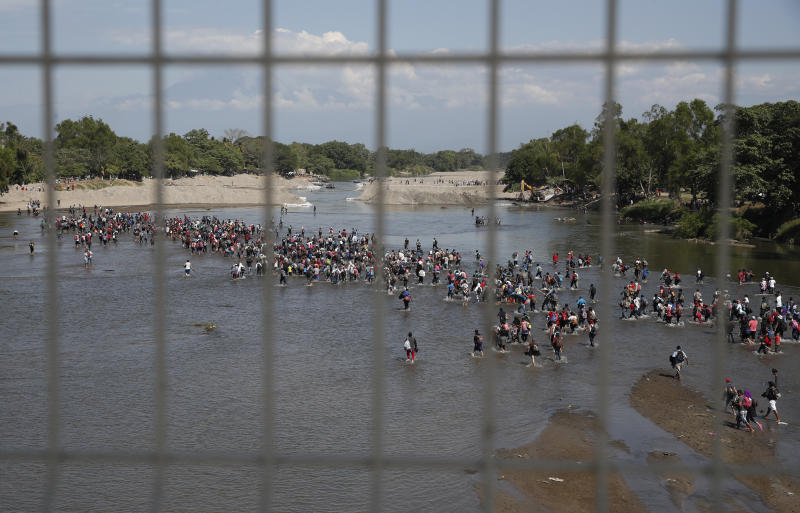Seen through the fence on the border bridge, Central American migrants cross the Suchiate River by foot from Tecun Uman, Guatemala, to Mexico, Monday, Jan. 20, 2020. More than a thousand Central American migrants hoping to reach United States marooned in Guatemala are walking en masse across a river leading to Mexico in an attempt to convince authorities there to allow them passage through the country. (AP Photo/Moises Castillo)