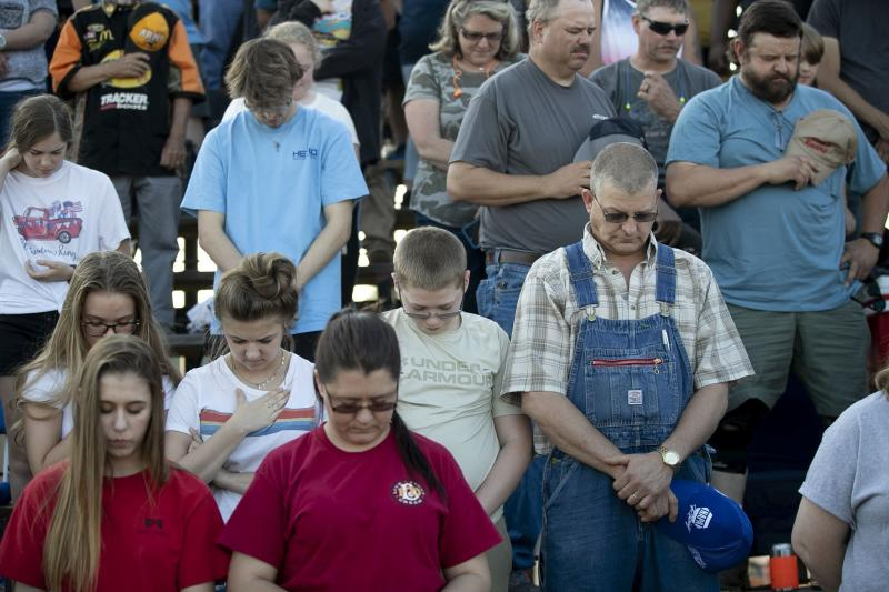 """In this Saturday, May 23, 2020 photo, race fans pray at the Ace Speedway on in the rural Alamance County community of Altamahaw near Elon, N.C. North Carolina Gov. Roy Cooper's administration has ordered closed a small stock-car track that's allowed large crowds to gather repeatedly for weekend races well above COVID-19 limits for mass gatherings. Cooper's health secretary says Ace Speedway in Alamance County is an """"imminent hazard"""" for the virus' spread and can't reopen unless it creates a safety plan to keep fans away. (Robert Willett/The News & Observer via AP)"""