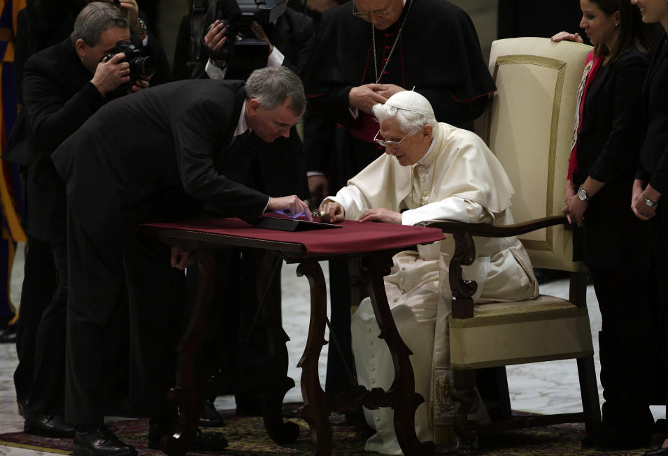 """Pope Benedict XVI pushes a button on a tablet at the Vatican, Wednesday, Dec. 12, 2012. In perhaps the most drawn out Twitter launch ever, Pope Benedict XVI pushed the button on a tablet brought to him at the end of his general audience Wednesday. It read: """"Dear friends, I am pleased to get in touch with you through Twitter. Thank you for your generous response. I bless all of you from my heart.""""Later in the day he was to respond to a few messages sent to him from around the world.As the countdown to his first tweet from his Twitter handle (at) Pontifex neared, the pope had garnered nearly 1 million followers in the eight languages of his account. (AP Photo/Gregorio Borgia)"""