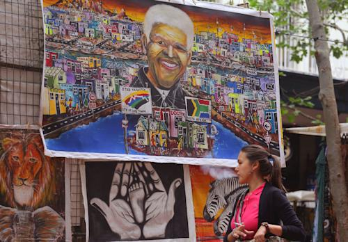 """A woman walks past a painting with the face of former South African president Nelson Mandela, central, in a street that sells African style art to tourist in the city of Cape Town, South Africa, Wednesday, Dec. 4, 2013. Ailing former South African President Nelson Mandela is not """"doing well"""" but is continuing to put up a courageous fight from his """"deathbed,"""" members of his family have told the South African Broadcasting Corporation in an interview. (AP Photo/Schalk van Zuydam)"""