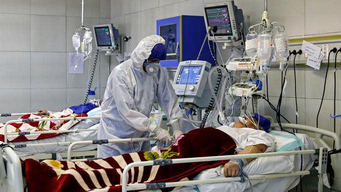 Petugas medis merawat seorang pasien yang terinfeksi virus corona atau COVID-19 di sebuah rumah sakit di Teheran, Iran, Minggu (1/3/2020). Kasus virus corona di Iran mengalami lonjakan tajam dalam beberapa hari. (Ali Shirband/Mizan News Agency via AP)