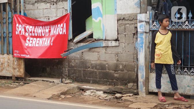 Seorang anak berdiri dekat poster protes warga terhadap pembangunan flyover di kawasan Tanjung Barat, Jakarta, Rabu (15/7/2020). Dalam poster protes tersebut, warga menuntut agar pembayaran pelunasan pembebasan lahan segera diselesaikan secara serentak. (Liputan6.com/Immanuel Antonius)