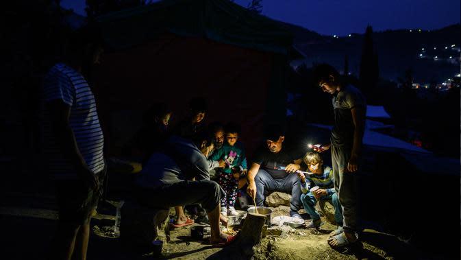 Para imigran menyiapkan makanan mereka di dekat sebuah kamp pengungsi di pulau Samos, Yunani (13/11/2019). Ribuan imigran berjuang untuk menemukan ruang di perbukitan di atas kota, membuat rumah sementara dari bahan bangunan apa pun yang dapat mereka temukan. (AFP Photo/Angelos Tzortzinis)