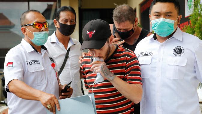 Petugas polisi mengawal Warga Negara Asing (WNA) asal Inggris, Collum (tengah) dan asal Australia, Aaron Wayne Coyle (belakang) di Mapolresta Denpasar, Bali, Kamis (3/9/2020). Kedua WNA tersebut ditahan karena mengedarkan narkoba jenis sabu dan ekstasi di wilayah Bali. (AP Photo/Firdia Lisnawati)