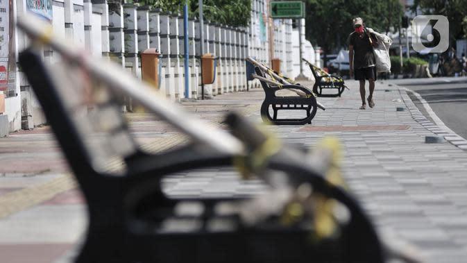 Pemulung melintasi deretan bangku trotoar yang disegel garis pembatas dan ditutupi bambu, Rawamangun, Jakarta, Minggu (3/5/2020). Bangku trotoar di sepanjang jalan Rawamangun disegel untuk mencegah kerumunan warga sebagai upaya memutus rantai penyebaran COVID-19. (merdeka.com/Iqbal S. Nugroho)