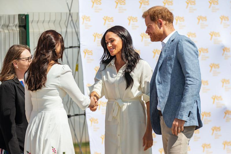 Meghan Markle and Prince Harry shaking hands with a charity worker in South Africa