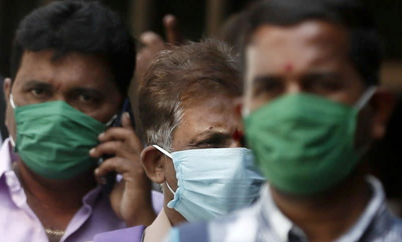 FILE PHOTO: Men wearing protective masks walk inside the premises of a hospital where a special ward has been set up for the coronavirus disease in Mumbai