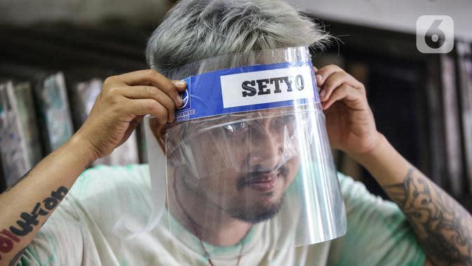 Bucek mengenakan face shield di workshopnya di kawasan Bekasi, Jawa Barat, Rabu (3/6/2020). Pemerintah mewajibkan petugas pelayanan, pedagang, serta pekerja toko swalayan dan mal mengenakan face shield saat fase new normal diterapkan. (Liputan6.com/Faizal Fanani)