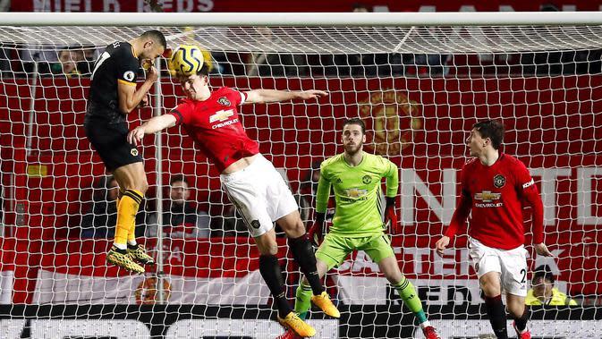 Bek Manchester United, Harry Maguire, duel udara dengan pemain Wolverhampton Wanderers, Romain Saiss, pada laga Premier League di Stadion Old Trafford, Sabtu (1/2/2020). Kedua tim bermain imbang tanpa gol. (AP/Martin Rickett)