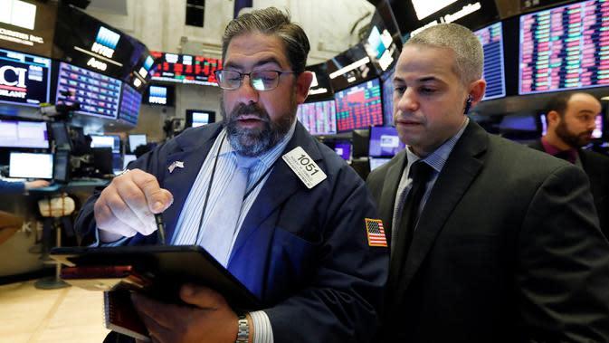 Director of Trading Floor Operations Fernando Munoz (kanan) saat bekerja dengan pialang Robert Oswald di New York Stock Exchange, AS, Rabu (11/3/2020). Bursa saham Wall Street jatuh ke zona bearish setelah indeks Dow Jones turun 20,3% dari level tertingginya bulan lalu. (AP Photo/Richard Drew)