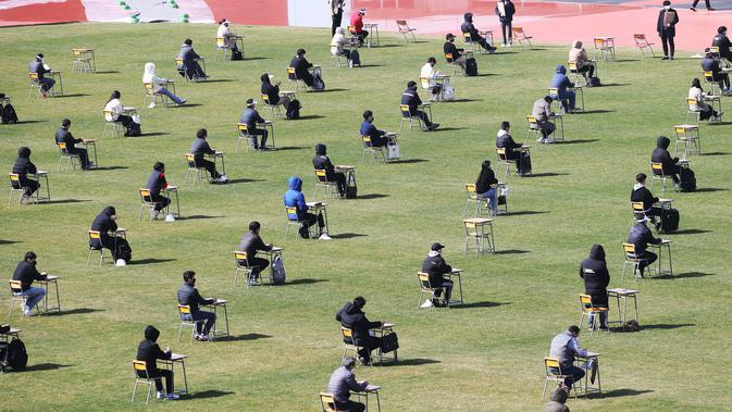 Pelamar kerja saat mengikuti ujian tertulis selama tes rekrutmen untuk Ansan Urban Corporation di stadion Wa di Ansan, Korea Selatan (4/8/2020). Korporasi memutuskan untuk mengadakan tes rekrutmen mereka di stadion terbuka sebagai bagian dari tindakan pencegahan Covid-19. (AP Photo/Hong Ki-won)