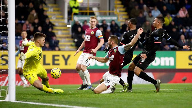 Kiper Burnley Nick Pope (kiri) menepis tendangan dari pemain Manchester City Gabriel Jesus (kanan) pada pertandingan Liga Inggris di Turf Moor, Burnley, Inggris, Selasa (3/12/2019). The Citizens mencukur Burnley 1-4, Gabriel Jesus mencetak dua gol. (Martin Rickett/PA via AP)