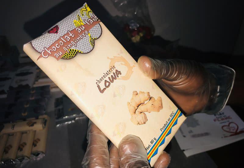 A worker holds a packaged bar of chocolate at the Lowa Chocolate Factory in Goma