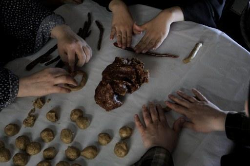 Palestinian women make traditional date-filled cookies in preparation for the Eid al-Fitr holiday at their home in Rafah in the southern Gaza Strip on August 12, 2012. Muslims around the world are preparing to celebrate the Eid al-Fitr holiday next week, which marks the end of the fasting month of Ramadan.  AFP PHOTO/ SAID KHATIB