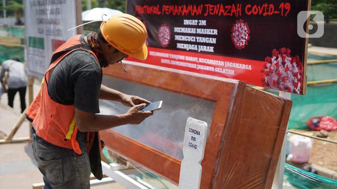 REPLIKA JENAZAH KORBAN COVID-19: Pekerja mengambil gambar peti mati berisi jenazah korban COVID-19 di Tanjung Barat, Jakarta, Sabtu (5/9/2020). Pemerintah terus melakukan kampanye bahaya COVID-19 bagi masyarakat guna menekan angka positif dan kematian. (Liputan6.com/Immanuel Antonius)