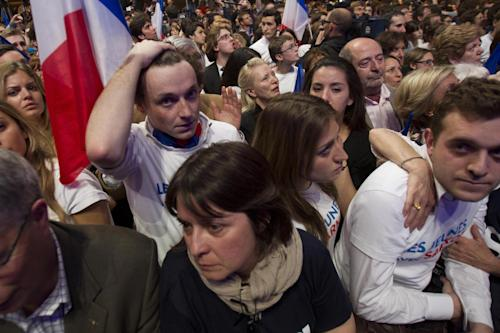A supporters of outgoing French President Nicolas Sarkozy's Union for a Popular Movement (UMP) holds his head as the preliminary results of the second round of the presidential elections were announced at UMP headquarters in Paris Sunday May 6, 2012. The first results showed a 52 percent lead for Socialist Party candidate Francois Hollande. (AP Photo/Michel Euler)