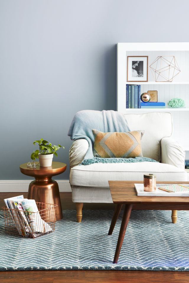<p>Pastel blue adds a fresh touch to this living room, while wood pieces and metallic accents create depth. <br></p>