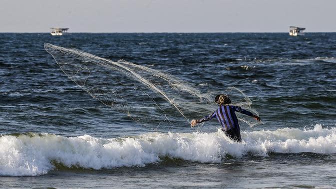 Seorang nelayan Palestina melemparkan jala ikan saat menangkap ikan di Laut Mediterania, Rafah, Jalur Gaza, Rabu (2/9/2020). (SAID KHATIB/AFP)
