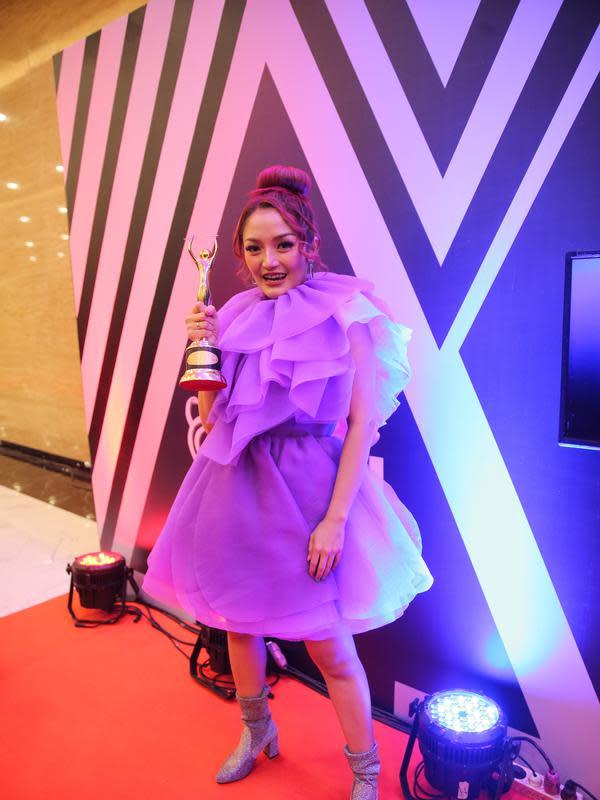 Siti Badriah juga cantik menggemaskan dengan busana berwarna ungunya dan berlayer. Senyuman pun sangat semringah, terlebih ia berhasil membawa pulang piala kemenangan kategori artis solo pria/wanita dangdut kontemporer terbaik. (Adrian Putra/Fimela.com)
