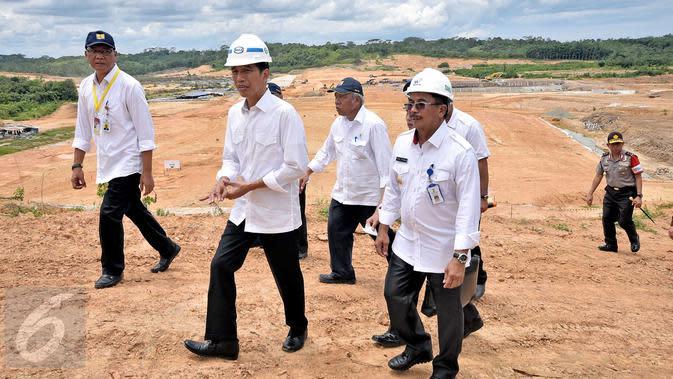 Presiden Jokowi (tengah) didampingi para menteri meninjau proyek pembangunan Jalan Tol Balikpapan-Samarinda di Desa Karangjoang, Kalimantan Timur, (24/3). Proyek sempat terhenti selama 5 tahun namun kini dilanjutkan kembali. (Setpres/ Agus Suparto)