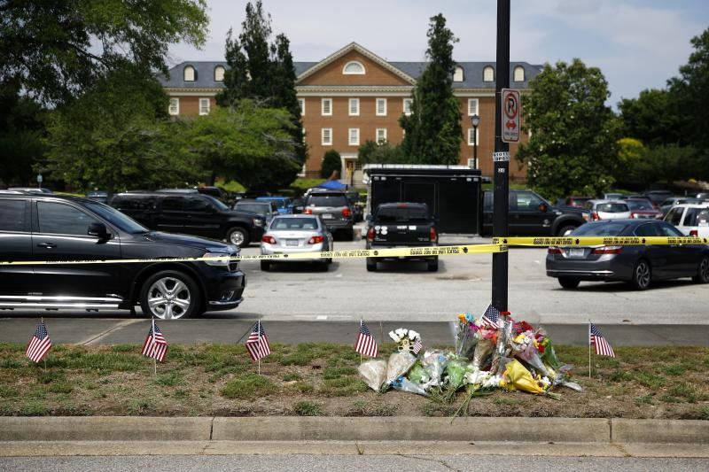 FILE - In this June 1, 2019, file photo, a makeshift memorial rests at the edge of a police cordon in front of a municipal building that was the scene of a shooting in Virginia Beach, Va. As the shooting's one-year anniversary approaches, some of the victim's family members say the rampage is effectively forgotten. (AP Photo/Patrick Semansky, File)