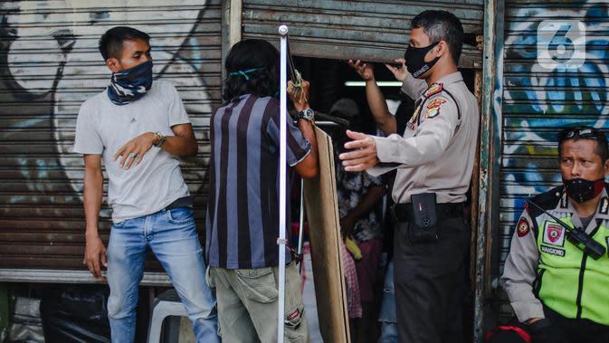Polisi menertibkan pedagang yang nekat berjualan saat masa pandemi COVID-19 di kawasan Pasar Tanah Abang, Jakarta, Jumat (22/5/2020). Gubernur DKI Jakarta Anies Baswedan menambah PSBB selama 14 hari mulai tanggal 22 Mei 2020. (Liputan6.com/Faizal Fanani)