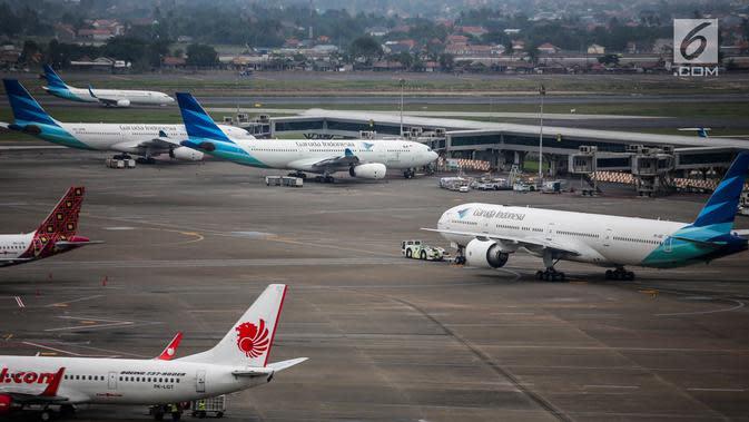 Pesawat maskapai Garuda Indonesia terparkir di areal Bandara Soekarno Hatta, Tangerang, Banten, Kamis (16/5/2019). Pemerintah akhirnya menurunkan tarif batas atas (TBA) tiket pesawat atau angkutan udara sebesar 12-16 persen yang berlaku mulai Kamis hari ini. (Liputan6.com/Faizal Fanani)