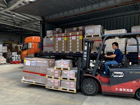 Forklift drivers move cartons of PPE goods to a cargo terminal at the Pudong International Airport before they go through a customs clearance process. Photo: Daniel Ren