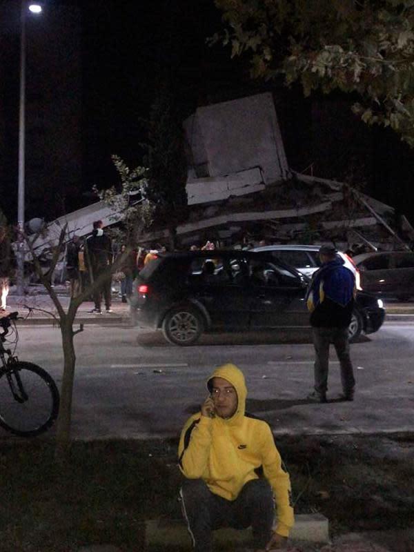 Seorang pria berbicara di ponsel ketika yang lain melihat kerusakan bangunan setelah gempa bumi di Durres, Albania barat, Selasa (26/11/2019). Gempa bumi bermagnitudo 6,4 mengguncang Albania, Selasa dini hari yang menyebabkan beberapa bangunan dan gedung permukiman runtuh. (AP Photo)
