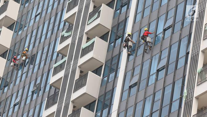 Pekerja membersihkan kaca gedung bertingkat di Jakarta, Kamis (18/10). Kepala Divisi Komunikasi BPJS Ketenagakerjaan Irvansyah Utoh Banja mengatakan, BPJS Ketenagakerjaan menargetkan kepesertaan BPJS Ketenagakerjaan 2018. (Liputan6.com/Immanuel Antonius)
