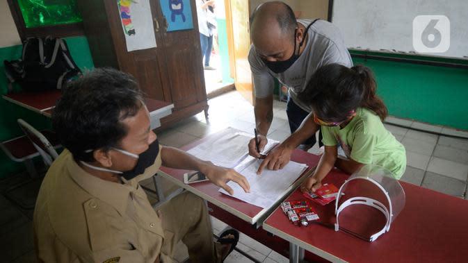 Guru membagikan dua kartu perdana Tri dan Telkomsel beserta kuota gratis kepada wali murid di SDN Serua Indah I dan II, Ciputat, Tangerang Selatan, Senin (15/9/2020). Program Kartu Perdana tersebut untuk mendukung kegiatan belajar secara online di masa pandemi covid-19. (merdeka.com/Dwi Narwoko)