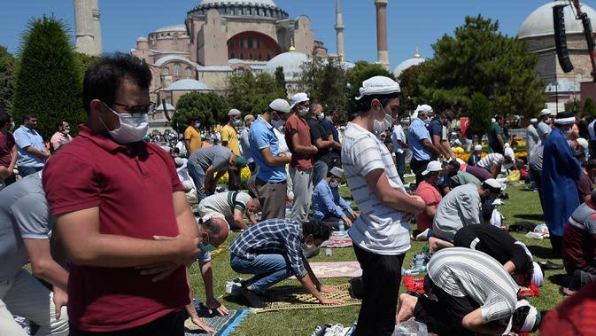 Umat Muslim berdoa saat menunaikan salat Jumat dengan latar belakang situs bersejarah Hagia Sophia di distrik bersejarah Sultanahmet di Istanbul, Jumat (24/7/2020). Hari ini, Hagia Sophia menyambut umat Islam melaksanakan salat Jumat pertama dalam 86 tahun.(AP Photo/Yasin Akgul)