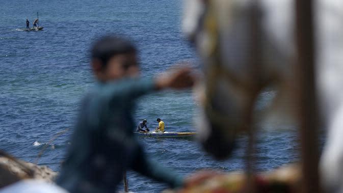 Nelayan memeriksa jaring mereka selama bulan suci Ramadan di pantai Kota Gaza, Palestina, Jumat (1/5/2020). (MOHAMMED ABED/AFP)