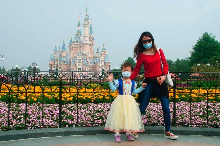 A small girl, wearing a face mask, waves in front of Shanghai Disneyland, supported by her mother.