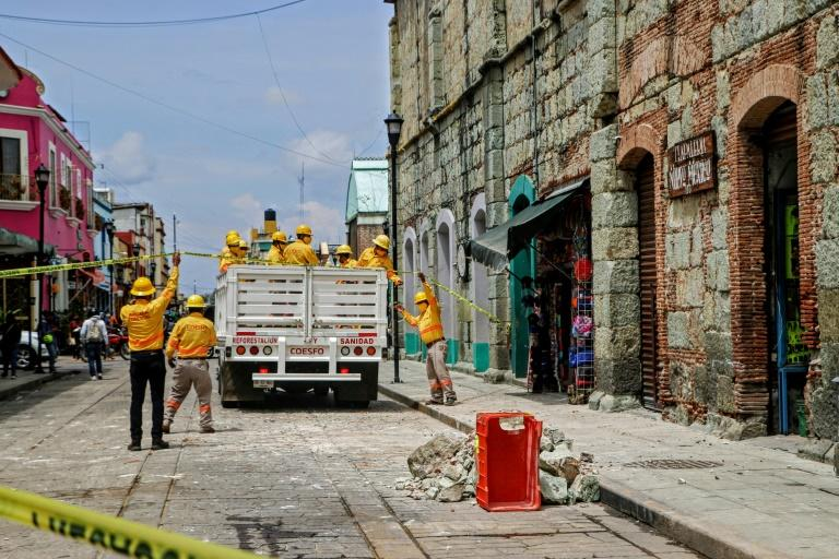 Workers remove rubble and place security tape alerting of a damaged building after a quake in Oaxaca, Mexico