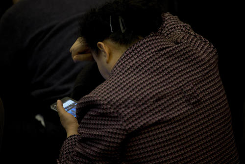 A relative of Chinese passengers aboard the missing Malaysia Airlines Flight MH370 uses her smartphone to watch a news conference held by the airlines' officials at a hotel ballroom in Beijing Monday, March 17, 2014. The search for the missing Malaysian jet pushed deep into the northern and southern hemispheres Monday as Australia took the lead in scouring the seas of the southern Indian Ocean and Kazakhstan - about 10,000 miles to the northwest - answered Malaysia's call for help in the unprecedented hunt. (AP Photo/Andy Wong)
