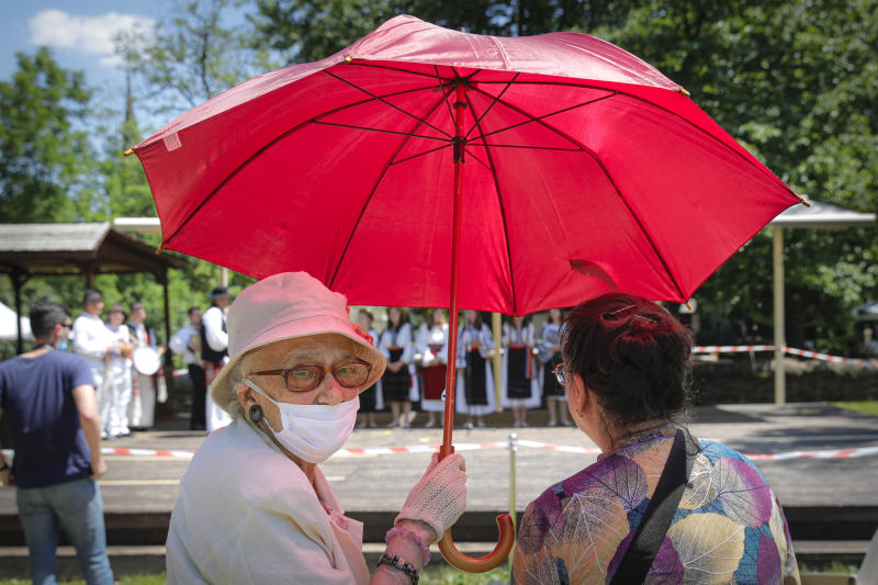 Two women, one wearing a face mask to combat the spread of the coronavirus, shield themselves from the sun under an umbrella while watching a folk group perform a summer solstice dance at the DImitrie Gusti Village Museum in Bucharest, Romania, Saturday, June 27, 2020. (AP Photo/Vadim Ghirda)