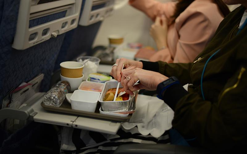 Image of passenger enjoying in-flight breakfast on board of an international flight.