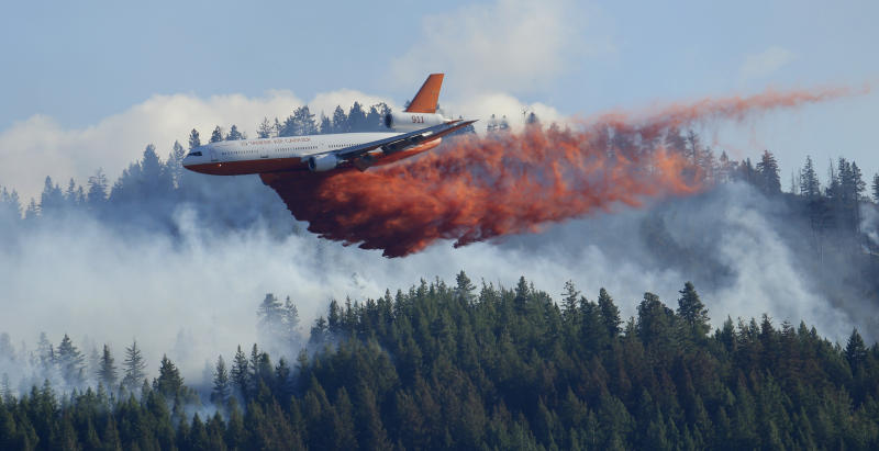 FILE - In this Aug. 21, 2015 file photo, a tanker airplane drops fire retardant on a wildfire burning near Twisp, Wash. Newly released national plans for fighting wildfires during the coronavirus pandemic are hundreds of pages long but don't offer many details on how fire managers will get access to COVID-19 tests or exactly who will decide when a crew needs to enter quarantine. (AP Photo/Ted S. Warren, File)