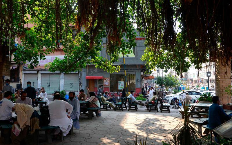 People sit at tables in the Pindi food street market in Rawalpindi as lockdown eases - FAROOQ NAEEM/AFP