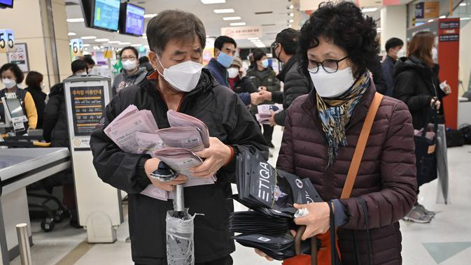 Orang-orang membeli masker di toko ritel di kota tenggara Daegu, Selasa (25/2/2020). Otoritas Korea Selatan (Korsel) melaporkan 60 kasus baru Virus Corona COVID-19di negeri itu pada hari ini, Selasa (25/2), sehingga kini total 893 orang terinfeksi virus tersebut. (Jung Yeon-je / AFP)