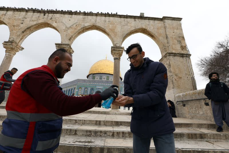 A visitor gets a cleaning gel for his hands in front of the Dome of the Rock in the compound known to Muslims as Noble Sanctuary and to Jews as Temple Mount, in Jerusalem's Old City