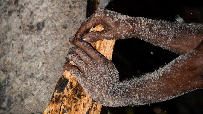 Gambar pada 9 Februari 2020 menunjukkan pekerja mengolah potongan pohon sagu menjadi tepung di sebuah desa di Meulaboh, provinsi Aceh. Tepung sagu adalah jenis tepung yang berasal dari pohon rumbia atau pohon aren, dan pohon jenis ini banyak ditemukan bagian timur. (CHAIDEER MAHYUDDIN/AFP)