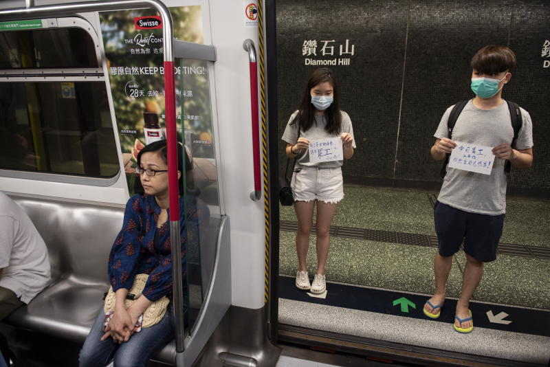 Protesters hold placards while blocking the doors of a Mass Transit Railway (MTR) subway train from closing as they disrupt its service in Diamond Hill MTR station, Hong Kong.