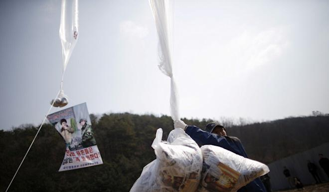 A North Korean defector living in the South holds a balloon containing leaflets. Photo: Reuters