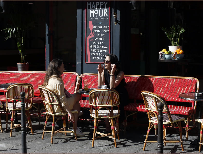 Women sit on the terrace of a cafe in Paris, Tuesday, June 2, 2020. Parisians who have been cooped up for months with take-out food and coffee will be able from Tuesday to savor their steaks tartare in the fresh air and cobbled streets of the City of Light once more -- albeit in smaller numbers. (AP Photo/Thibault Camus)