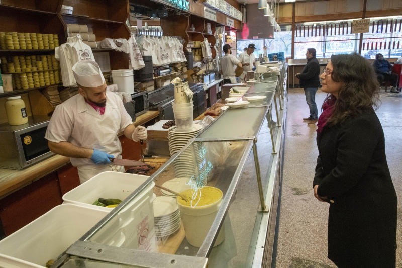 In this March 19, 2020 photo,  Adar Beck, right, of Jersey City, N.J., stands at a distance from the counter as she watches a cutter carve her order of pastrami at Katz's Delicatessen on the Lower East Side of New York. The iconic eatery is only open for take out and delivery orders due to the coronavirus outbreak. (AP Photo/Mary Altaffer)